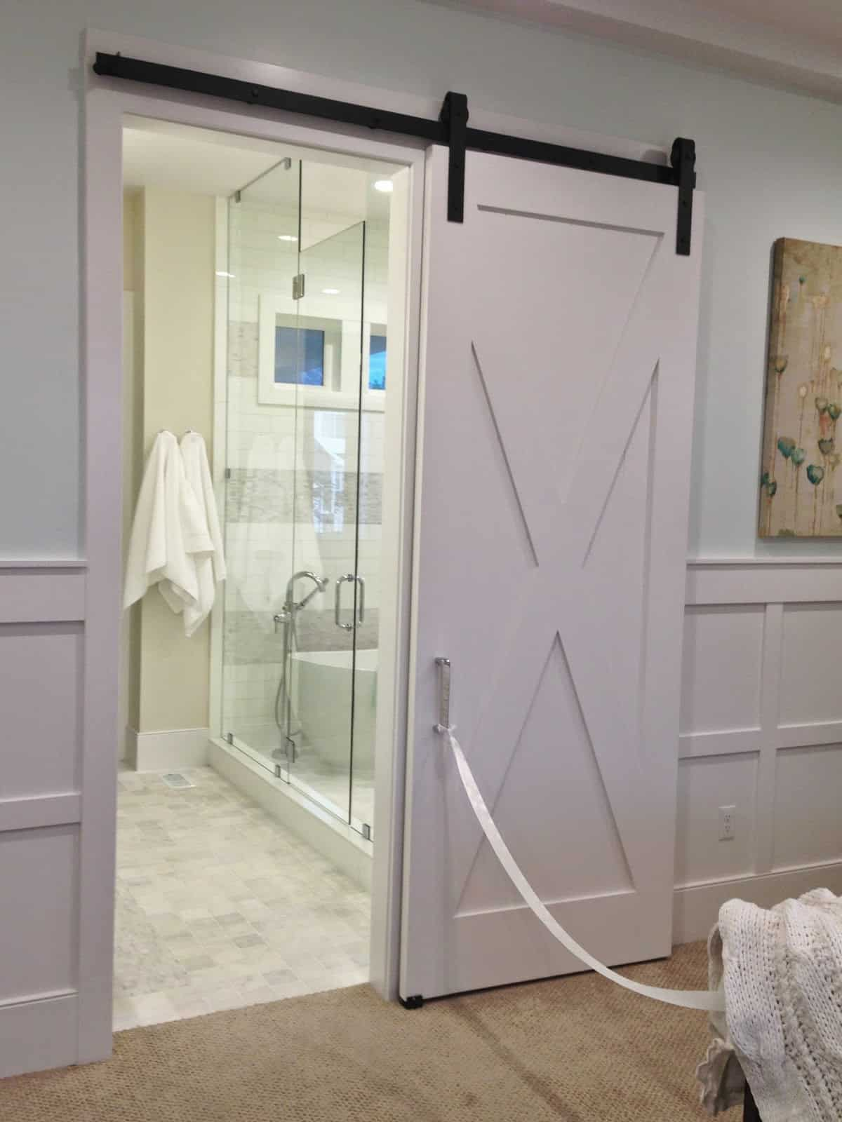 Simple, white barn doors can make all the difference when you're changing your bathroom doors for barn doors instead.