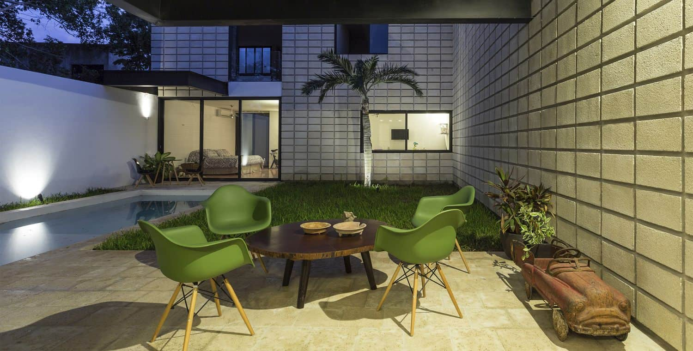 C Shaped Concrete Block Home Wraps Around Swimming Pool