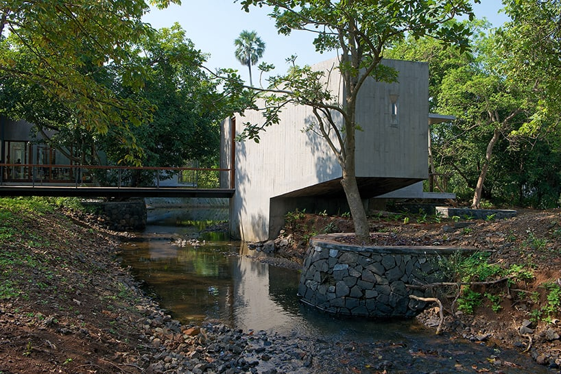 Steel Bridge over Stream Connects Private and Public Areas of Home