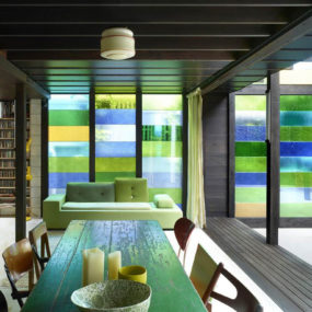 Cottage with Colored Glass Walls and Pre-existing Trees