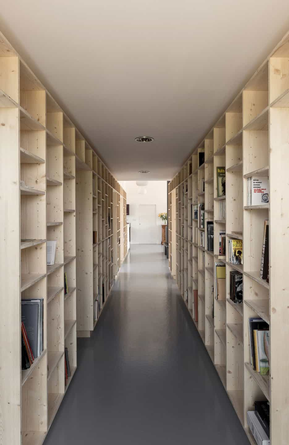 Country Home With Clean Lines Features Hallway Of Bookshelves