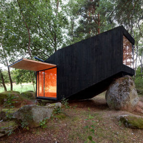 Cute Forest Cabin Supported by a Boulder