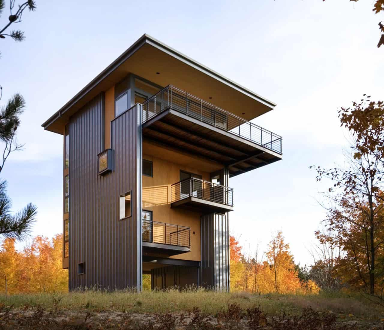 4 storey tall house reaches above the forest to see the lake for Lakehouse construction