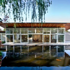Sustainable Home Wraps Around Man Made Pond and Lush Landscaping
