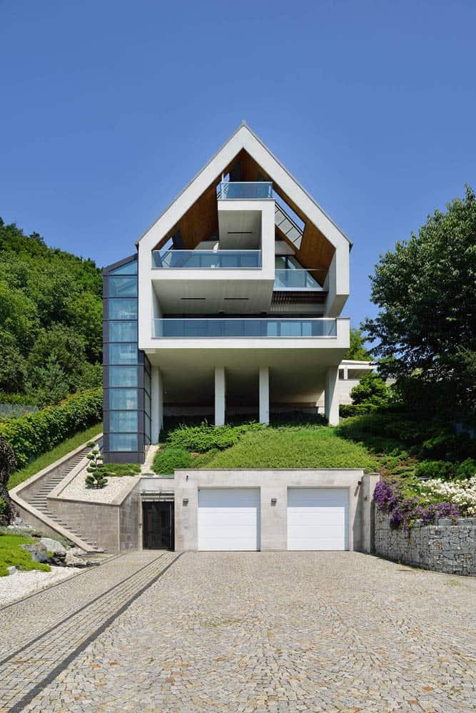 Gorgeous Glass Elevator connects Multiple Levels on Slope House