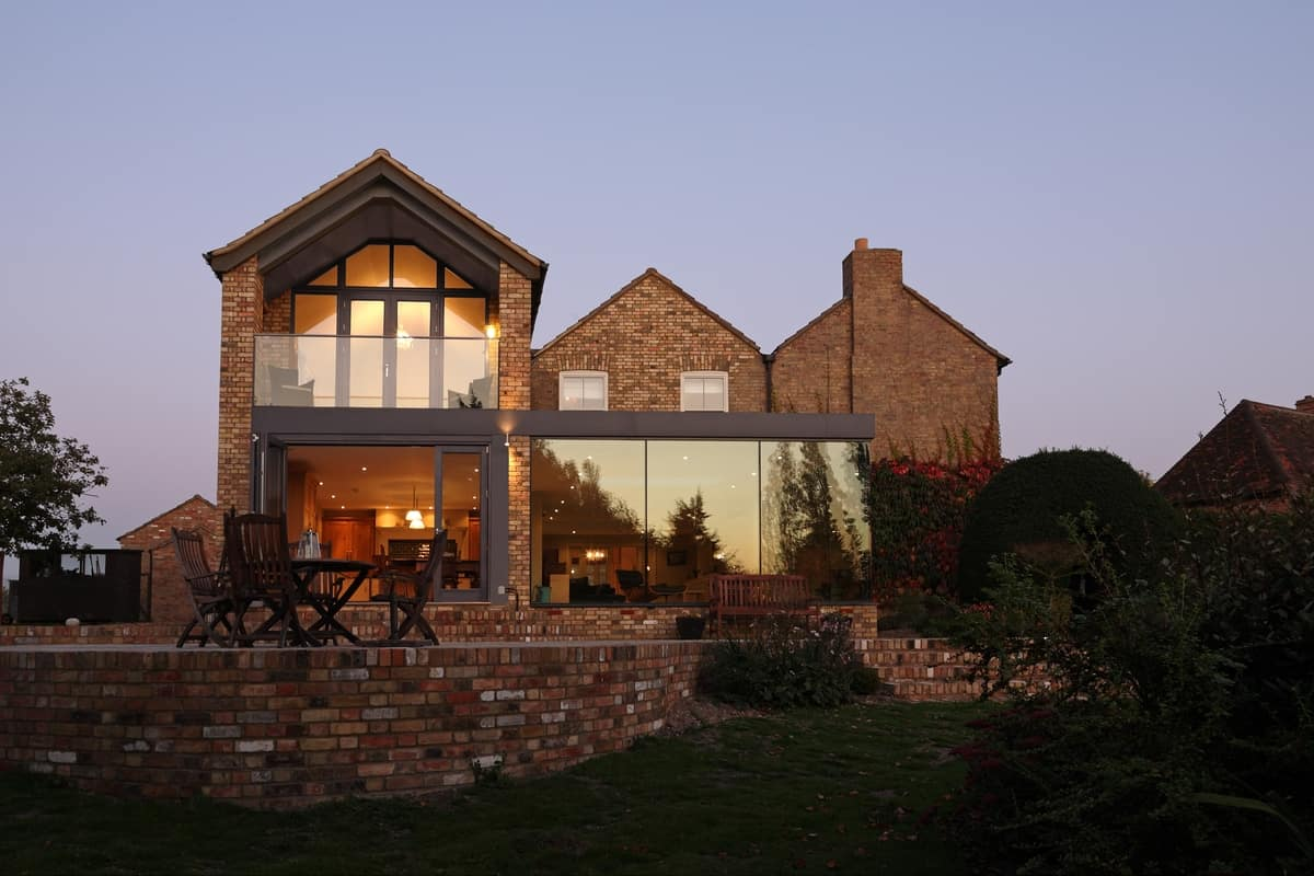 Modern glass addition to otherwise traditional home for Modern house designs uk