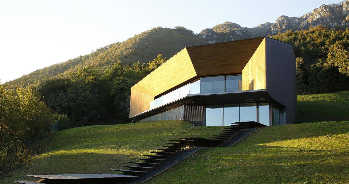 Alpine Villa Cleverly Uses Hillside to Form a Giant Wood Clad Courtyard