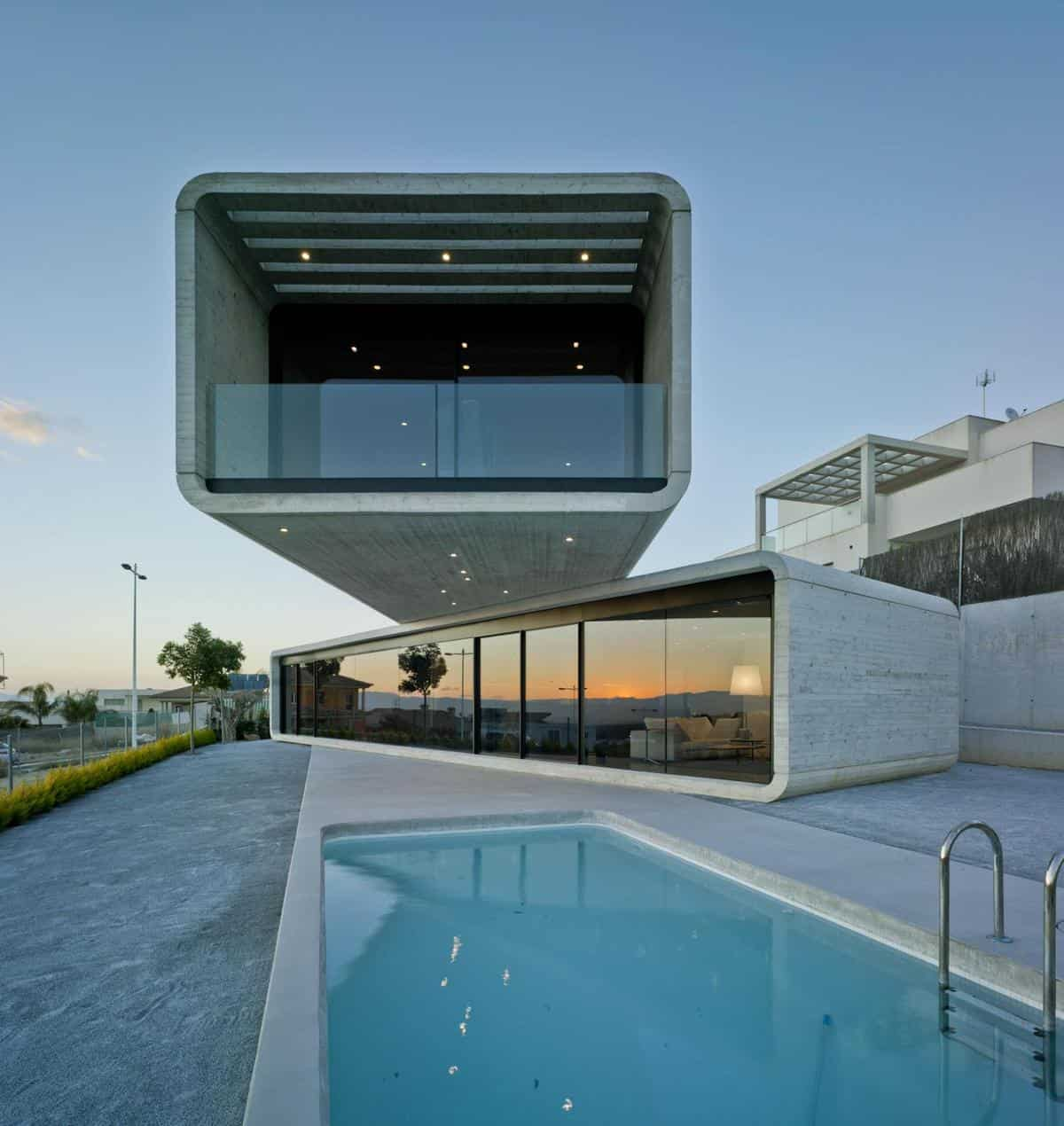 Concrete cantilever house extends 32 feet over the pool for Minimalist house definition