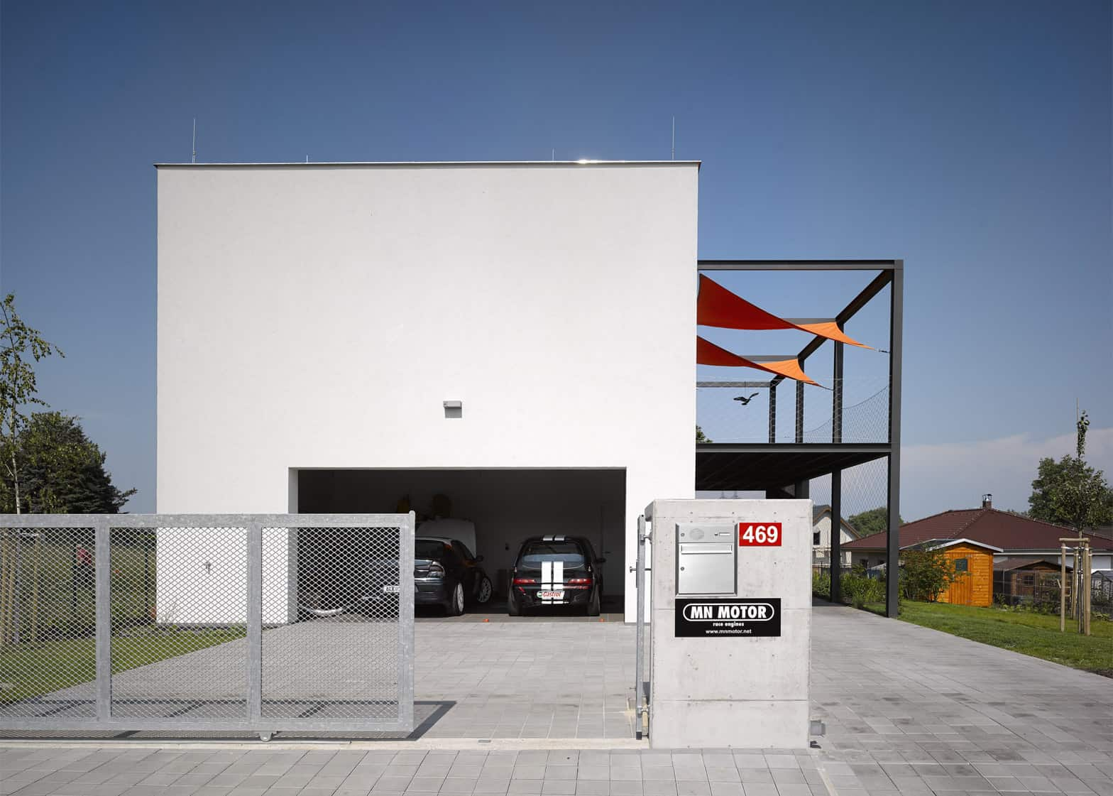 House for racing driver features main floor car shop for Main floor