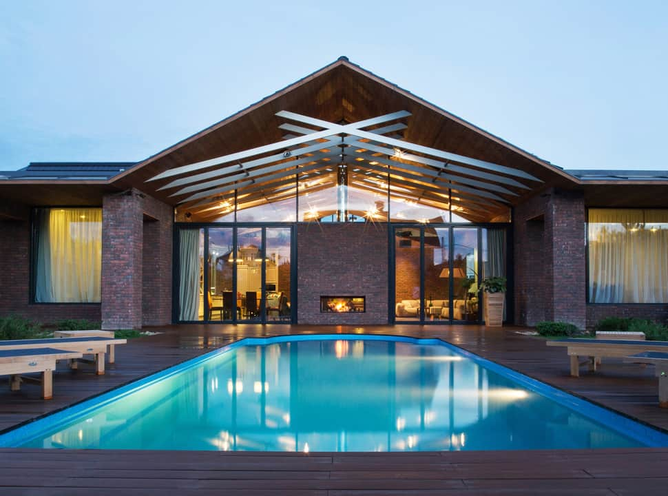 Exposed Trusses Create Artistic Composition Within Brick Country Home
