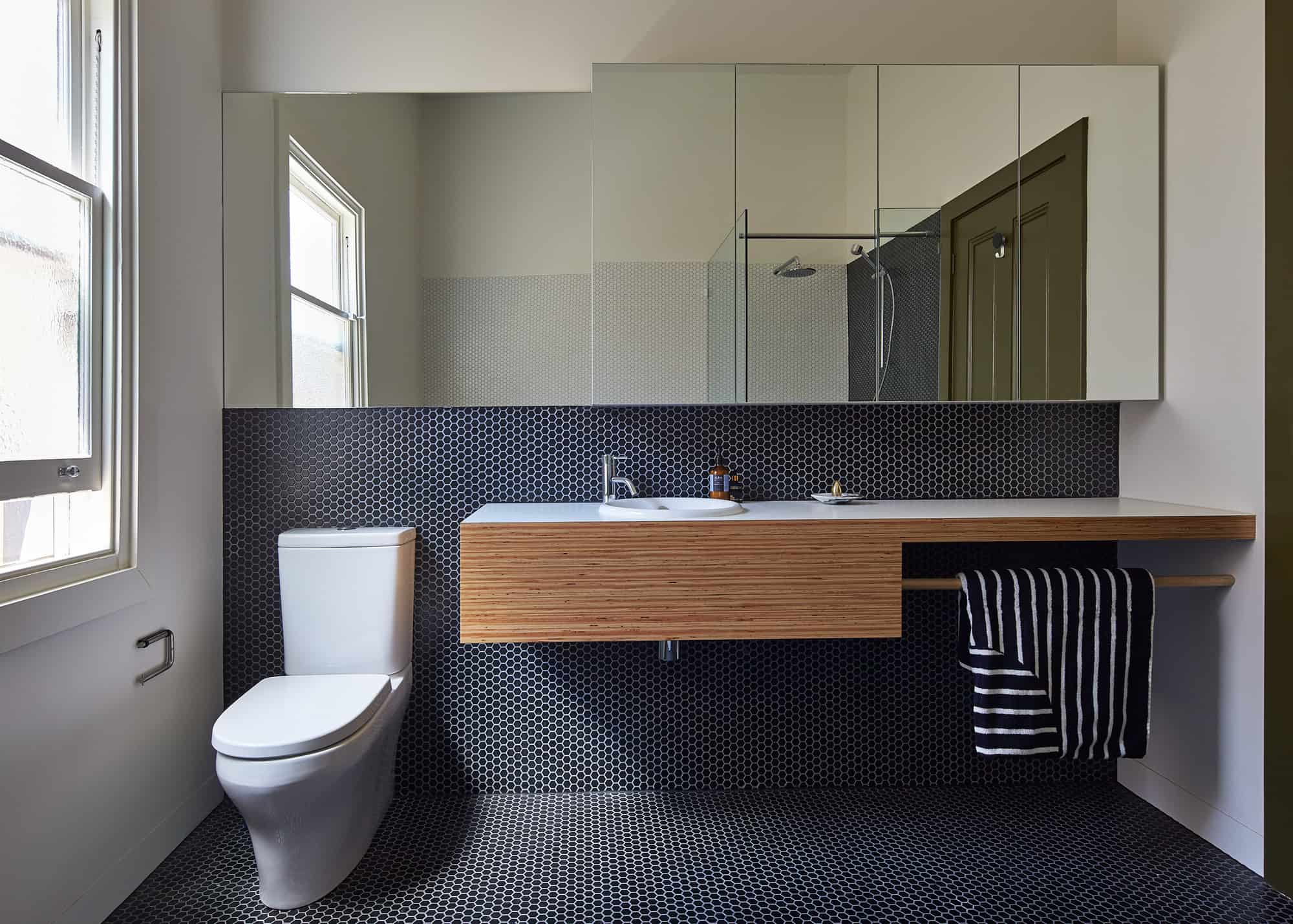 Cool Continuing the black theme the bathroom is covered in black penny tiles grouted white which picks up on the white veined black marble used on the