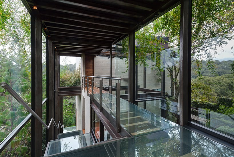 Outdoor elevated glass walkway connects two sections of house for Elevated modern house design