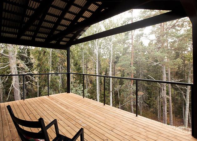 single-storey-summer-house-overlooks-forested-gorge-sweden-4-wrap-around-deck.jpg