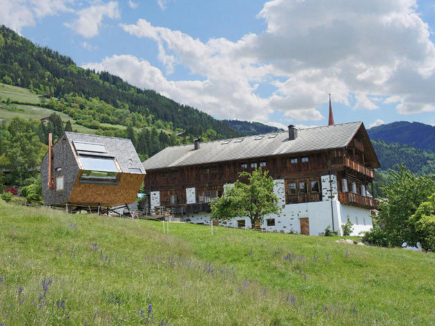 compact-irregularly-shaped-austrian-mountain-house-on-stilts-4-below-summer.jpg