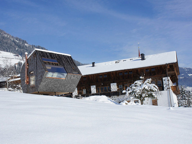 compact-irregularly-shaped-austrian-mountain-house-on-stilts-5-below-winter.jpg