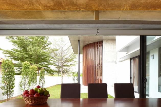 curved-stacking-glass-doors-surround-drum-shaped-room-voila-house-13-dining.jpg