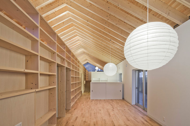 house-with-exposed-timber-rafters-bookshelf-columns-4-downstairs-night.jpg