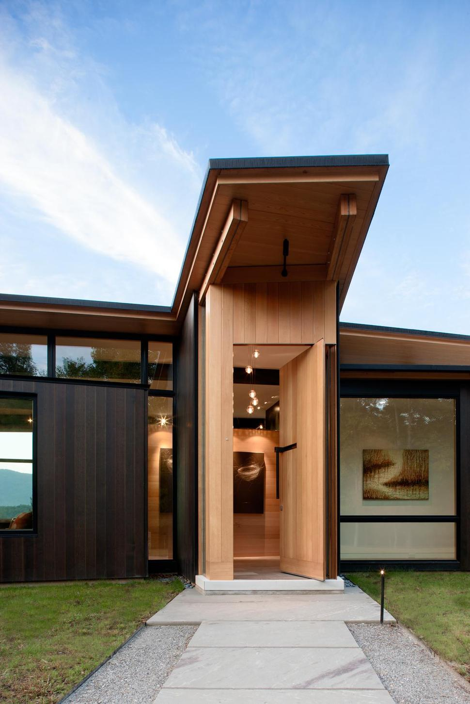 Minimalist silhouette and walls of glass define piedmont for Entrance from garage to house