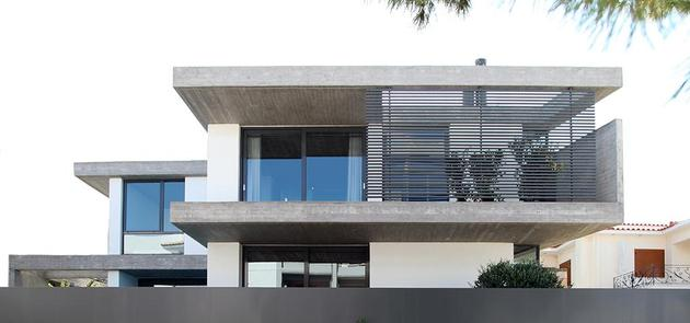 sleek athens house blends stone with concrete textures 2 front wall thumb 630x295 26216 Sleek Athens House Blends Stone With Concrete Textures