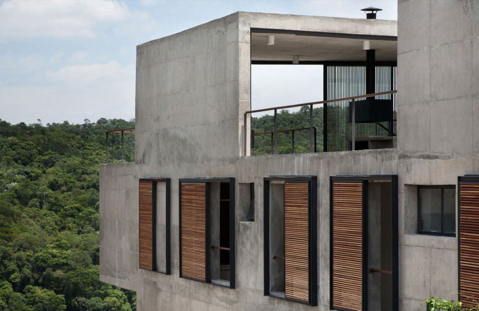 hillside house with 2 concrete volumes 2nd story entrance On concrete exterior walls