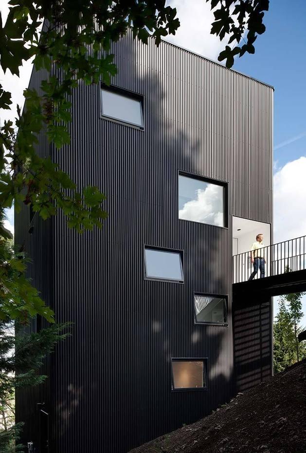 black-four-story-hillside-home-with-bridge-entry-path-3-left-front-below-bridge.jpg