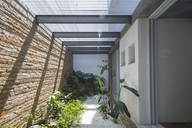brazilian-concrete-house-built-around-three-story-courtyard-tree-10-side-garden.jpg