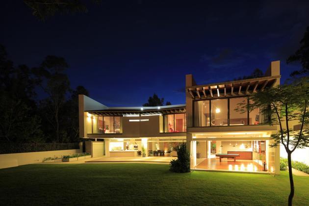 casa-siete-opens-wide-front-back-false-façade-29-backyard-evening.jpg