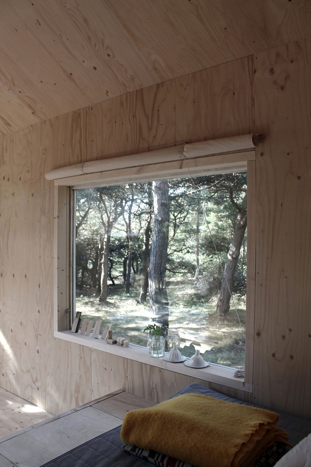 compact-plywood-pine-cabin-with-attached-sauna-11-back-window.jpg