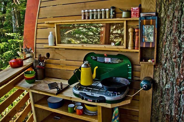 suspended-wooden-pod-cabin-built-around-tree-trunk-16-cooking-open-side.jpg