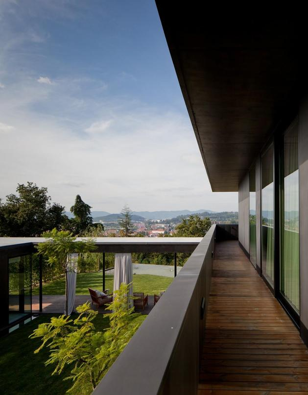 black-home-with-bright-interior-built-into-grassy-hillside-11-inside-upper-deck.jpg