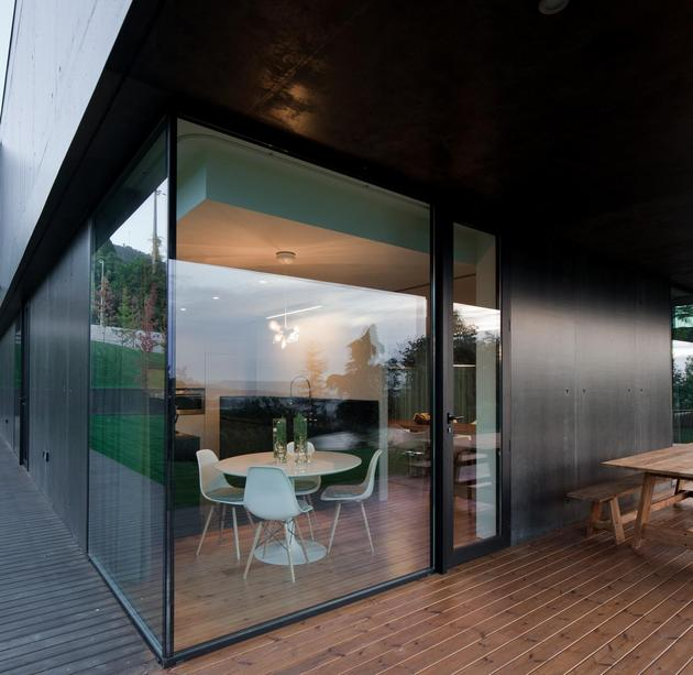 black-home-with-bright-interior-built-into-grassy-hillside-12-corner-room.jpg