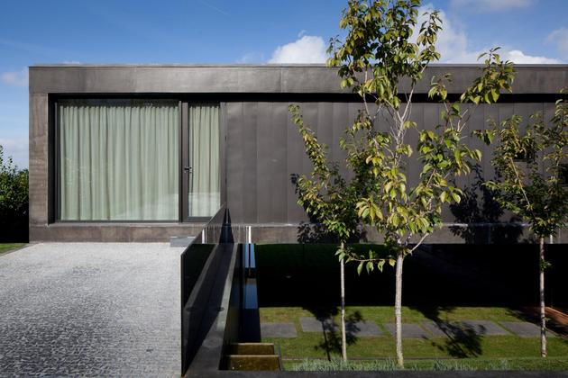 black-home-with-bright-interior-built-into-grassy-hillside-13-second-floor-deck-door.jpg