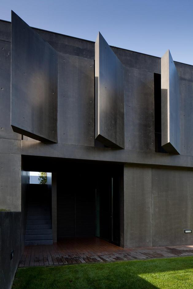 black-home-with-bright-interior-built-into-grassy-hillside-14-angled-concrete.jpg