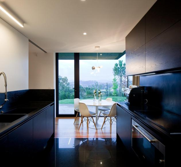 black-home-with-bright-interior-built-into-grassy-hillside-18-kitchen.jpg