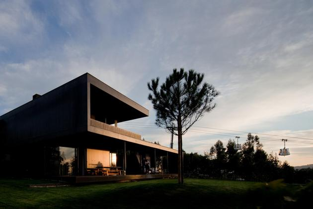 black home with bright interior built into grassy hillside 2 front angle shadows thumb 630xauto 31952 Home with an Indoor Lap Pool