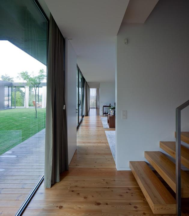 black-home-with-bright-interior-built-into-grassy-hillside-21-bottom-open-hallway.jpg