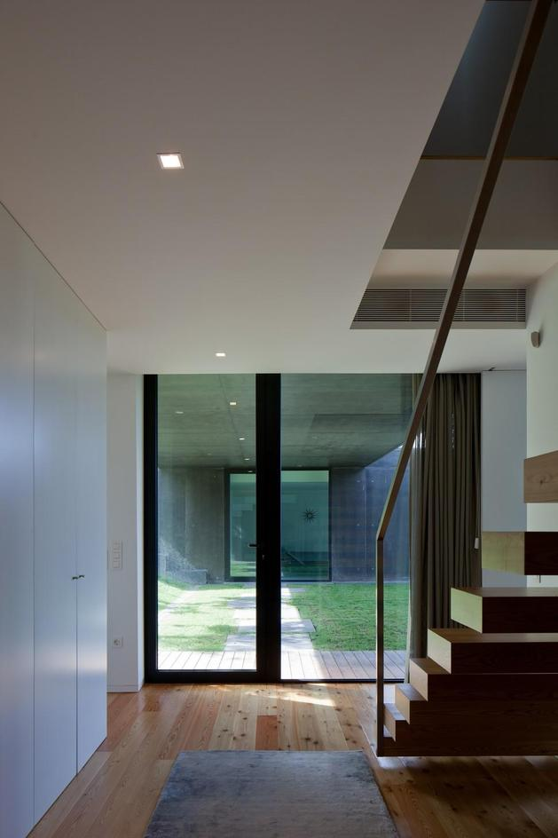 black-home-with-bright-interior-built-into-grassy-hillside-22-floating-stairs.jpg