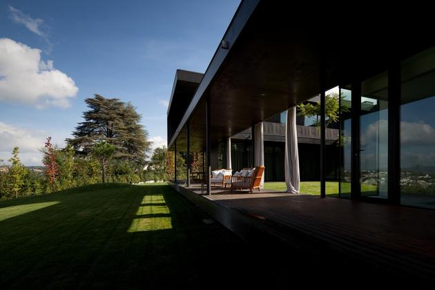 black-home-with-bright-interior-built-into-grassy-hillside-5-front-porch.jpg