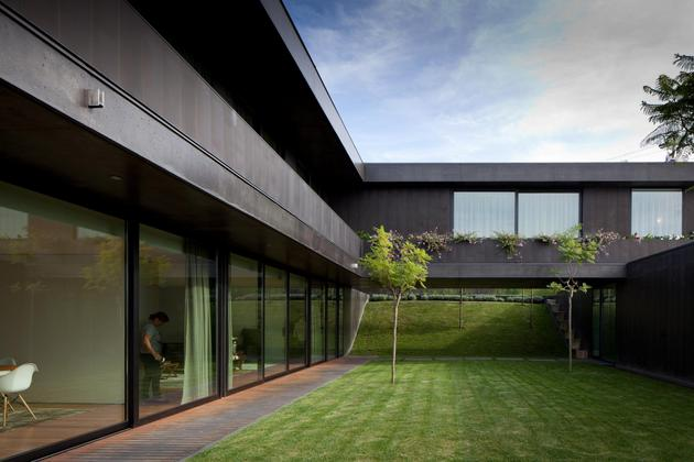 black-home-with-bright-interior-built-into-grassy-hillside-6-courtyard.jpg