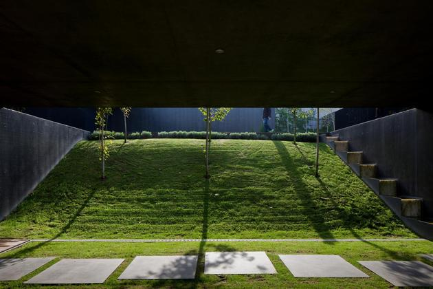 black-home-with-bright-interior-built-into-grassy-hillside-7-hill-between-walls.jpg