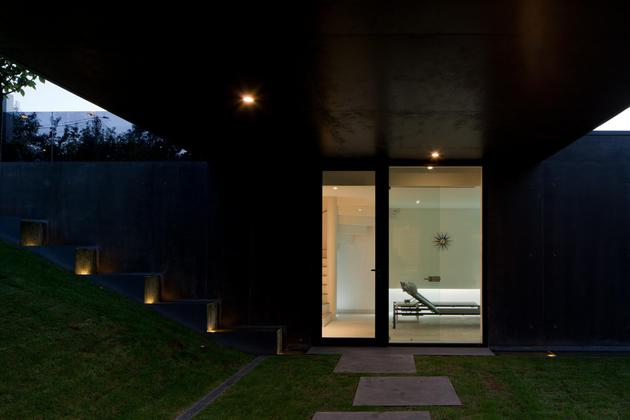 black-home-with-bright-interior-built-into-grassy-hillside-8-courtyard-door.jpg