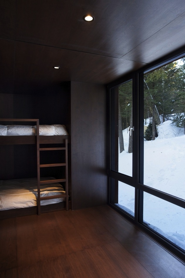 forest-getaway-cabin-dominated-by-warm-wood-boards-10-dark-bedroom.jpg