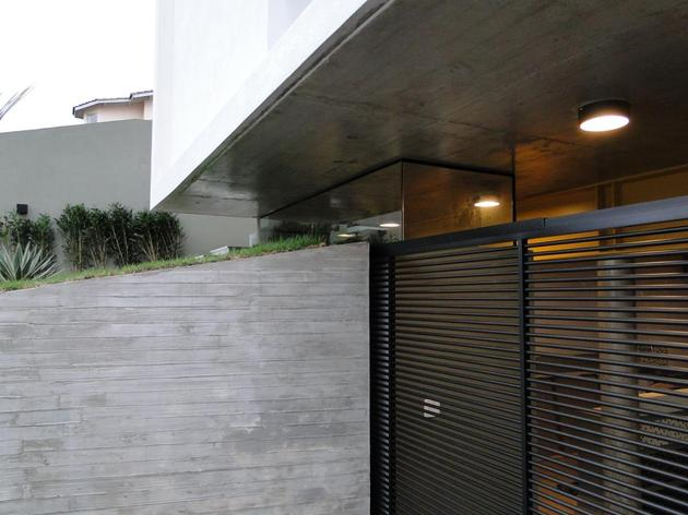 concrete-cube-home-supported-2-yellow-i-beams-3-garage-gate.jpg