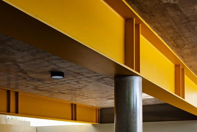 concrete-cube-home-supported-2-yellow-i-beams-4-garage-beams.jpg