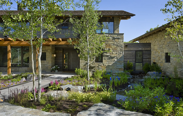 contemporary-stone-farmhouse-with-aged-wood-siding-segments-5-gardens.jpg