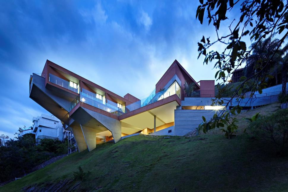 Sculptural concrete house built on a steep slope for Building house with side views