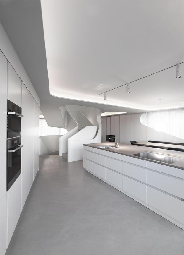 angular-modern-home-features-large-curvaceous-stairwell-inside-10-kitchen.jpg