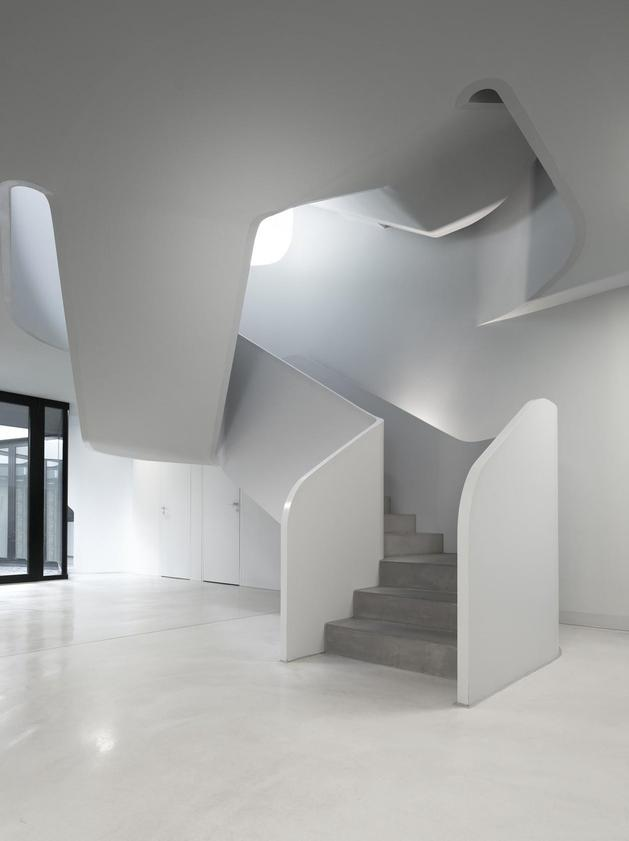 angular-modern-home-features-large-curvaceous-stairwell-inside-6-foyer.jpg