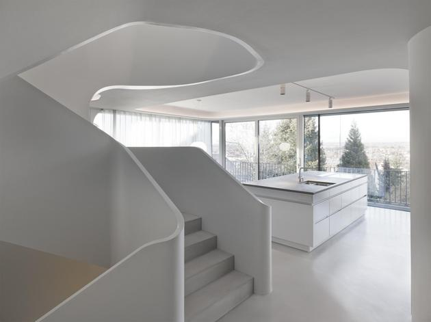 angular-modern-home-features-large-curvaceous-stairwell-inside-8-kitchen.jpg