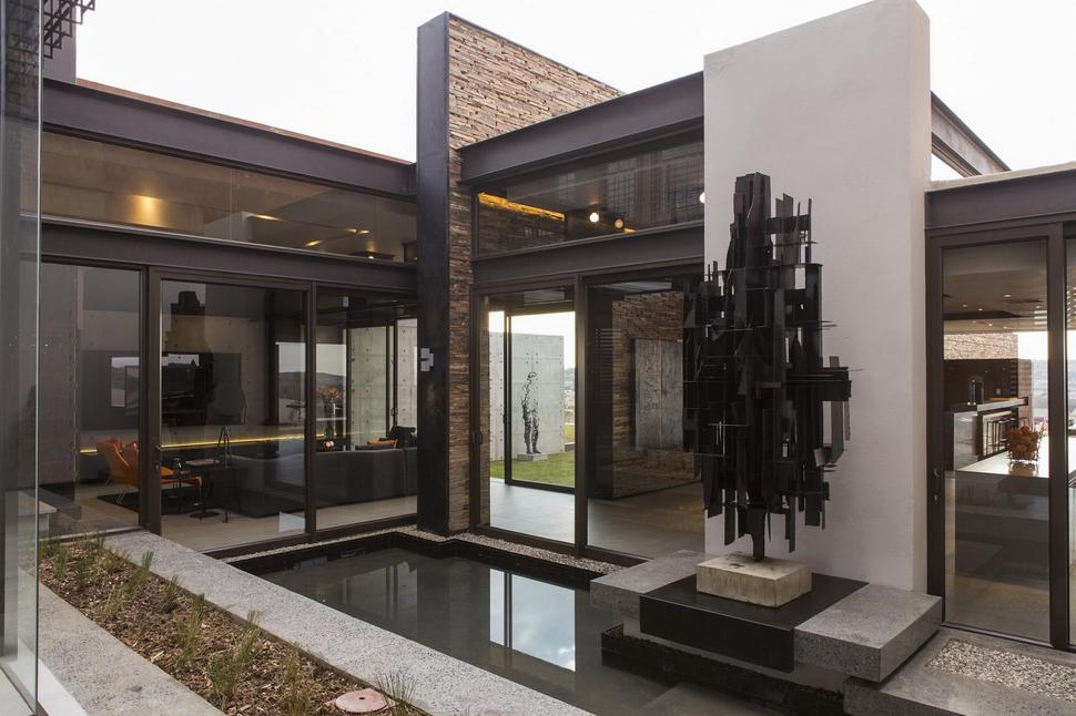 Geometric Concrete And Steel Home With Stone And Water